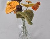 light orange, burgundy, yellow, and brown button flower bottle bouquet