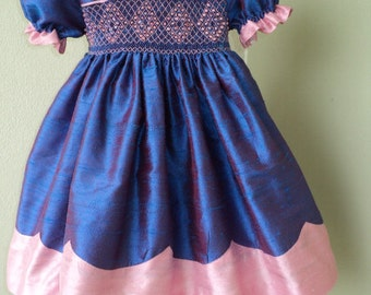 Girls smocked dupioni silk dress w/scalloped hem, ruffle trimmed sleeves, peter pan collar. Two colors of choice. Free bow.