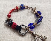 Handmade bracelet with silver, red and blue glass beads, tourmaline, japanese indigo fabric, red silk, antique hindu pendant  with bell