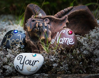 Hand-painted and decorated personalized name rocks create memorable table place settings. Delight your guests with these keepsake favours.