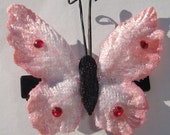 small embossed pink velvet butterfly hair clip with rhinestone details and antennae