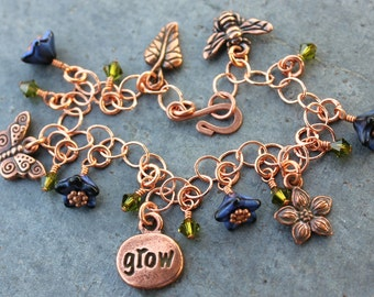 Copper garden charm bracelet with leaf, butterfly, flower, bee and Grow charms, deep blue glass flowers and olivine green Swarovski crystals