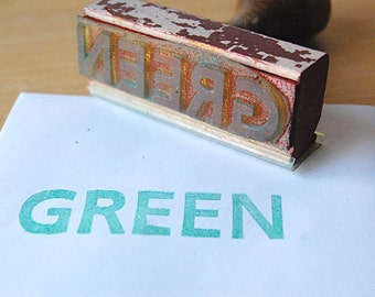 Vintage Wood Rubber Stamp of the Word Green in All Capital Letters.