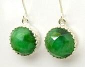 Emerald earrings set in silver around gemstone