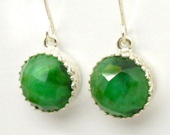 Emerald earrings set in silver around gemstone