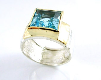 Blue topaz ring set in Yellow gold on a hammered silver wide band