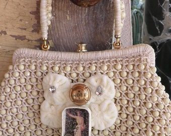 Chic, vintage purse with charming centerpiece of velvet roses, rhinestones, champagne charm and altered tin.