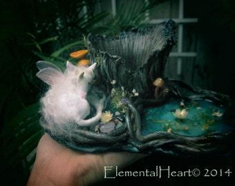 handmade unicorn faery sculpture in a woodland setting with crystal quartz