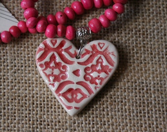 Pink ceramic heart necklace with wooden beads.