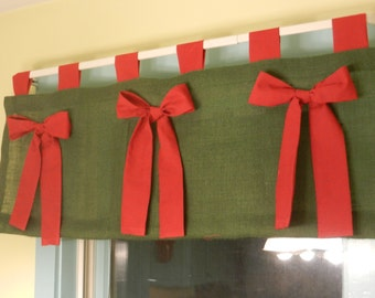 Green burlap valance with red bows and tabs.