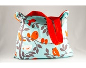 Foldable shopping bag lined in clear turquoise cotton with orange and white birds