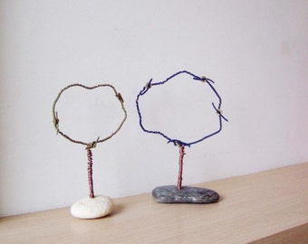 Wire tree sculptures on flat pebbles, metal and stone tree sculptures with green and blue cord, tree outlines on dark and white pebbles