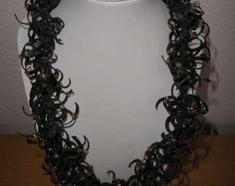 Necklace . Black rubber necklace.Each piece with  golden brown bead.Recycled and original art. Necklace is 21,66 inches long.