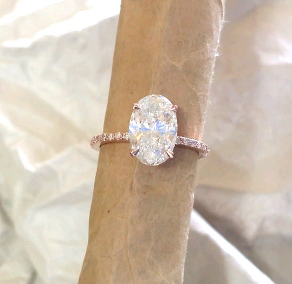 Oval engagement ring. featuring diamonds and Forever brilliant moissanite. pink gold