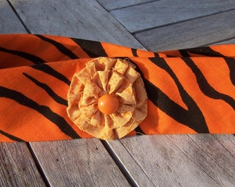 Orange and black bandana head band with  flower accent.
