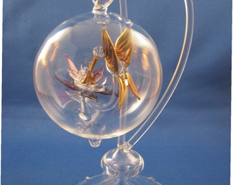 handblown glass hummingbird with columbine in a inclosed blown glass sphere