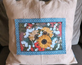 Appliqued throw pillow with a yellow textured front and a light blue textured back, with original floral painting applied to front.