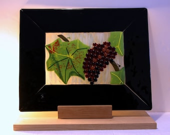 In a Vineyard - A Big Fused Glass Panel Showing a Purple Grape and Green Leaf, Framed in Black