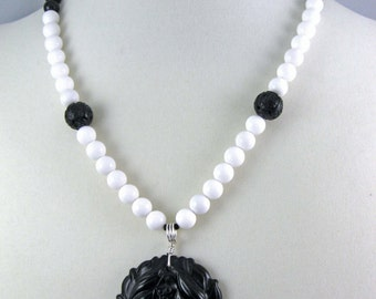 Black Lotus Necklace, carved flower pendant on black and white color block beads