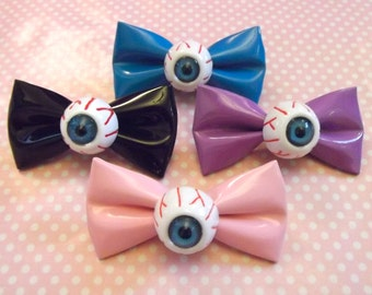 Creepy cute eyeball patent pvc bow hair clips in black, pink, blue, and purple