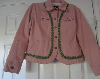 Pink denim jacket with green and black trim and four pockets.