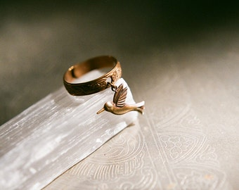 Adjustable vintage brass ring with embossed floral design and tiny hummingbird