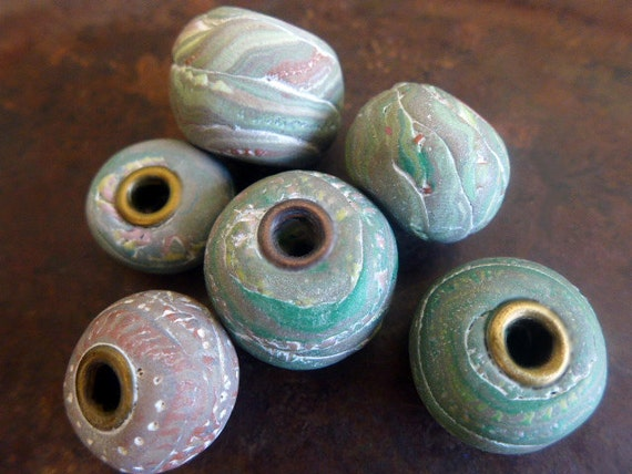 Orbitals. Polymer clay art beads, cored with layers of neutrals and brights.