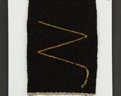 Tapestry Weaving. Black with Yellow, Green, and Red Design