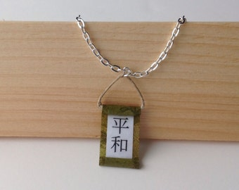 Peace in Japanese calligraphy on green scroll necklace