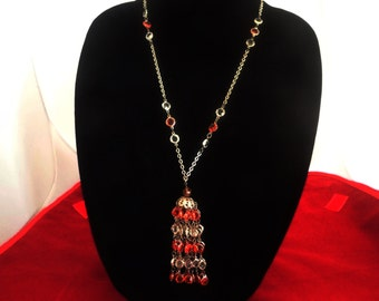 "Vintage lightweight gold tone 28"" necklace with 4"" center drape with orange and clear plastic accents  in great condition"
