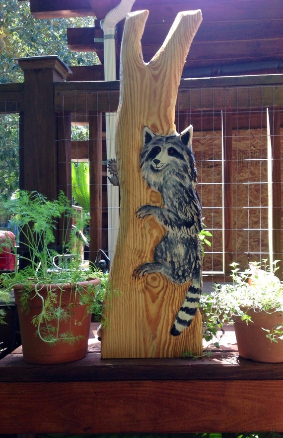 Raccoon in tree rustic woodland chainsaw wood by
