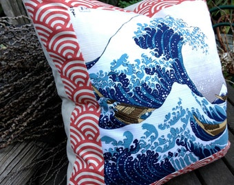 "Great Wave Off Kanagawa woodblock print, cushion pillow of iconic tsunami graphic by Hokusai and ""seigaiha"" pattern in terracotta."
