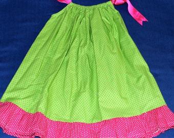 Polka dot green dress with pink ruffle and pink ties.