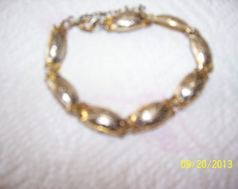 Goldish metal braclet with black and golden pattern