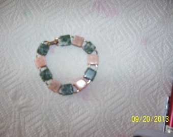 "Pink and green stone bracelet, 6-1/2"", set on goldish metal"