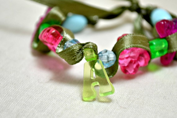 Kid's letter A bracelet.  Green ribbon. Colorful plastic beads. Stretchy bracelet. Ships free.