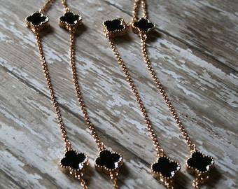 Long gold necklace with 3D black quatrefoil links necklace