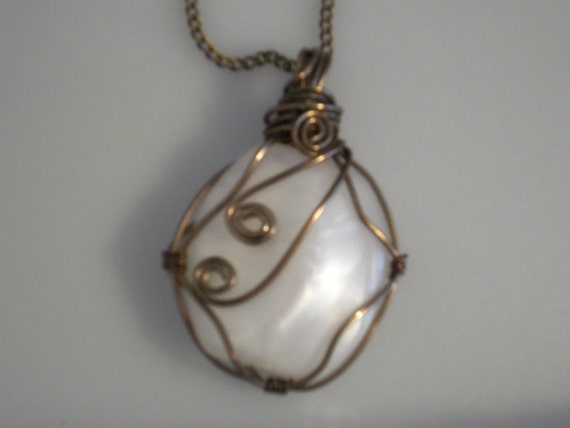 Wire wrapped cabochon pendant. White acrylic wrapped with bronze colored copper wire. Bronze chain.