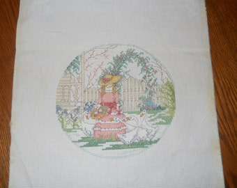 Finished counted cross stitch ready to frame. Delicate pastel  colors of little girl in pink feeding geese.