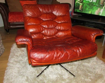 A Vintage De Sede swivel leather chair by Robert Haussman Mid Century one left