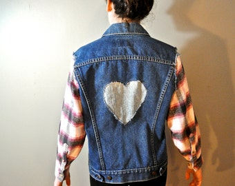 Upcycled Levi's denim jacket with plaid flannel sleeves, studs and cut out heart appliqué on the back. Girls XL/Women's S-M