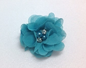 Hair clip with a feminine aqua bow accented by pearls and rhinestones in the center.