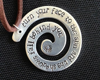 "Hand stamped aluminum swirl pendant/necklace with inspirational message: ""Turn your face to the sun and the shadows fall behind you"""