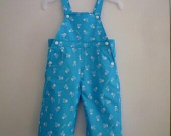 "Blue bib, baby size 9-12 months, 100% cotton, ""death's heads"" on a blue background"