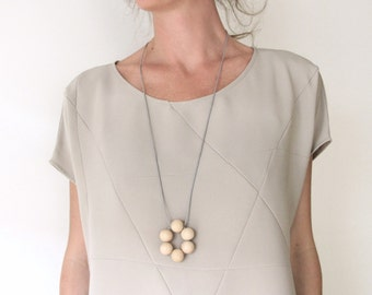 geometric necklace with natural wooden beads on a gray leatherstring