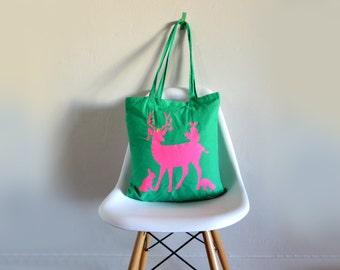 Green tote bag with neon pink animals. Deer, rabbit, squirrel, bird, mushroom.