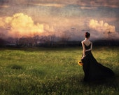 Going Home is a photographic print of a woman crossing a field at dusk, returning home.