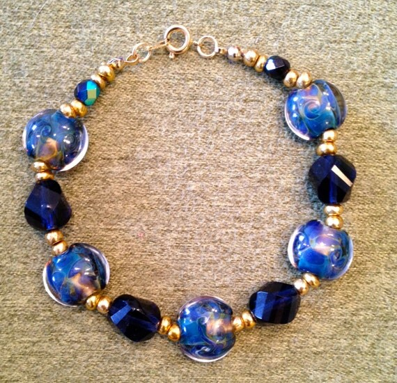 Bracelet with lampwork blue and gold Mediterranean lentil design glass beads, gold seed beads and dark blue Swarovski multifaceted crystals
