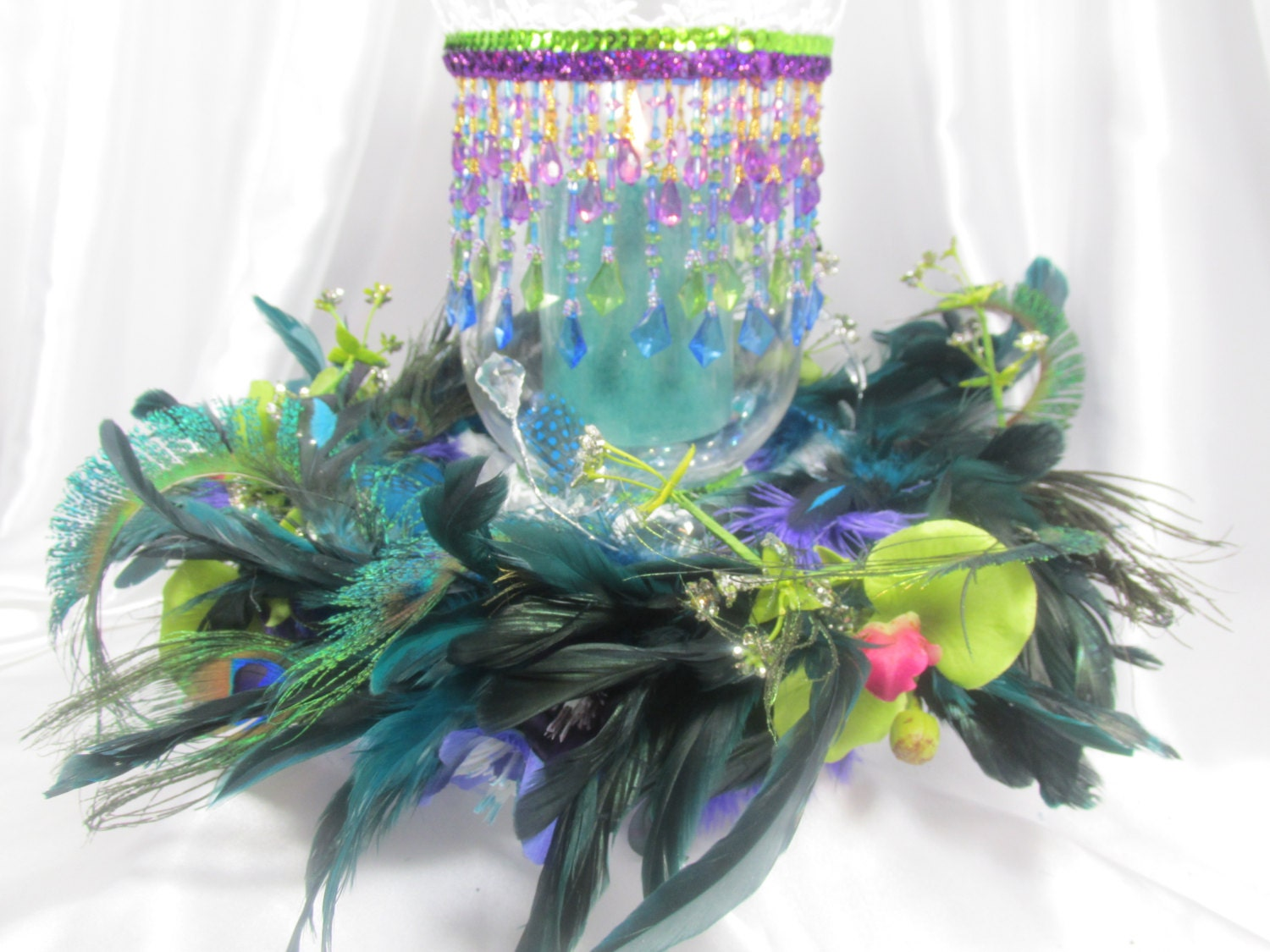 Peacock feathered wreath and beaded hurricane candle holder