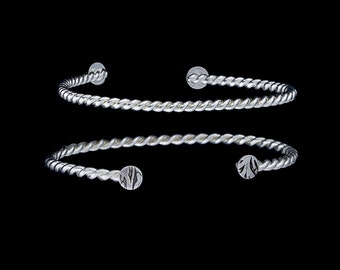Twisted Wire: stackable silver bracelets with etched circles on ends.